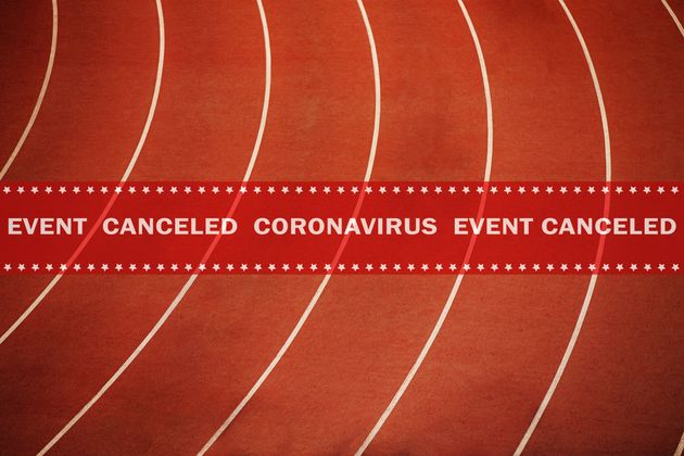warning tape event canceled coronavirus in background running athletics red track