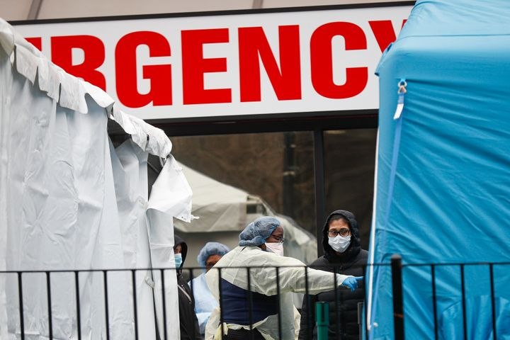 A medical worker directs a patient to enter a COVID-19 testing site at Elmhurst Hospital Center.