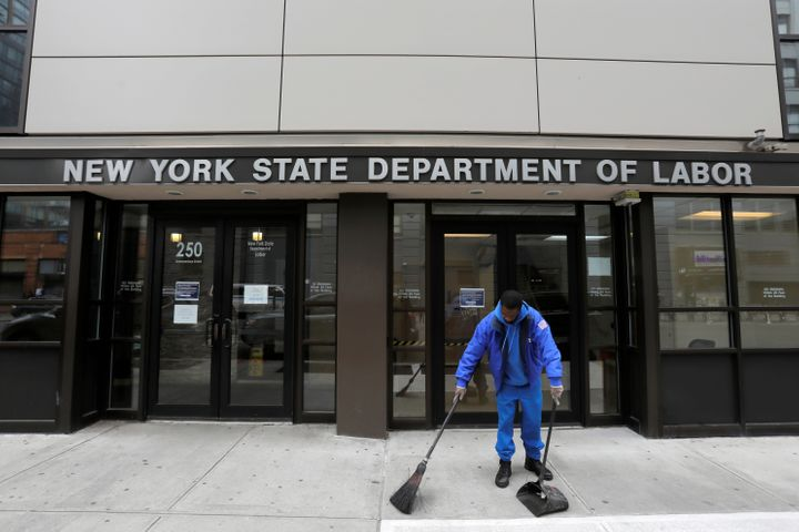 A person sweeps outside the entrance of the New York State Department of Labor offices, which closed to the public due to the