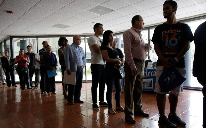 In this file photo, a group of people line up for unemployment benefits in a government office in Miami Lakes, Fla., July 19, 2016. Canada's unemployment rate is likely to hit a 70-year high amid the COVID-19 crisis, a new analysis says.