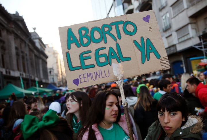 """A pro-choice activist holds a sign that reads in Spanish """"Legal abortion now"""" during a rally to legalize abortion outside Congress in Buenos Aires on May 28, 2019."""