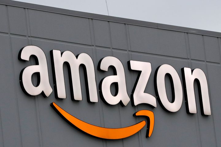 A sign is lit on the facade of an Amazon fulfillment center on Staten Island in New York. The company plans to hire another 1