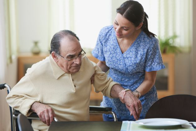 Nurse aiding an elderly man stand up from