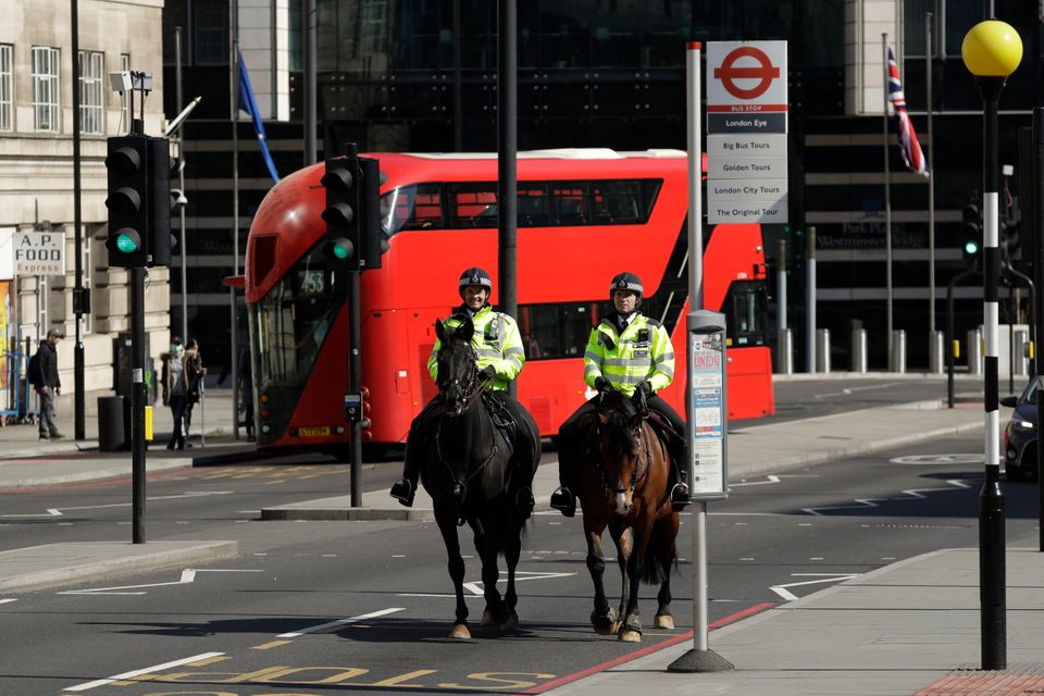 Two mounted police make their way over Westminster Bridge in