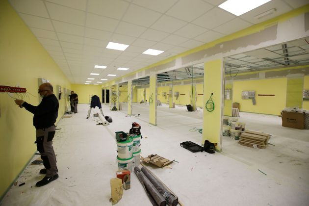 Workers operate to convert the university sports field into a new intensive care unit, outside the San...