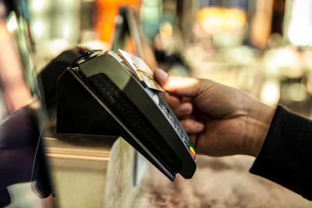 In this stock photo, a man's hand inserts a credit card into a payment terminal. The federal government...
