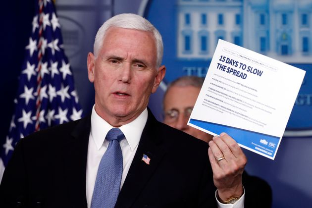 Vice President Mike Pence holds up a card about coronavirus prevention in the James Brady Briefing Room...