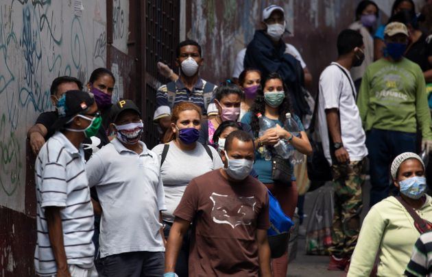 People line up to buy food and disinfectant, some wearing face masks as a preventive measure against...