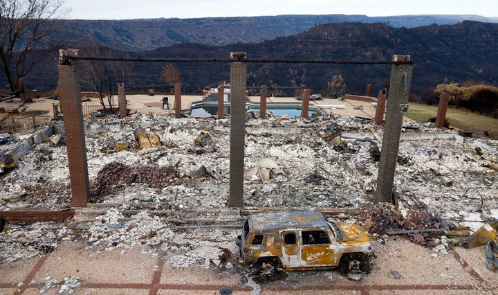 A burned-out vehicle rests in front of a home leveled by the Camp Fire in Paradise, California, in 2018.