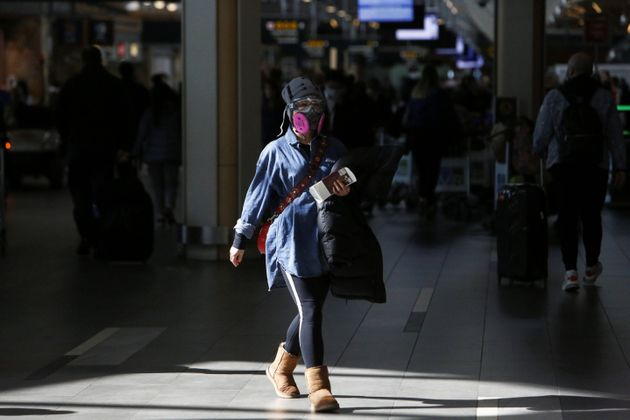 A woman wearing a protective face mask and goggles walks through Vancouver International Airport in Richmond,...