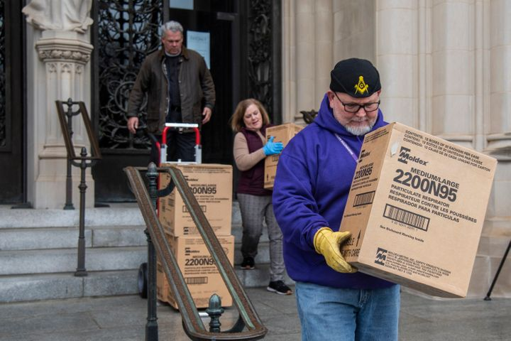 People transport boxes of N95 respirator masks out of the Washington National Cathedral on March 25, 2020.