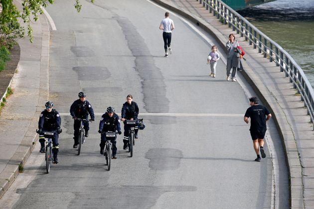 Des policiers patrouillent sur les bords de Seine à Paris le 20 mars, pour s'assurer du respect...