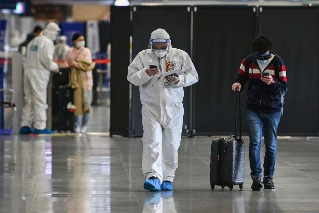 상하이 푸동 국제공항에서 보호복을 입은 공항 보안요원이 한 입국 승객을 안내하고 있다. 2020년