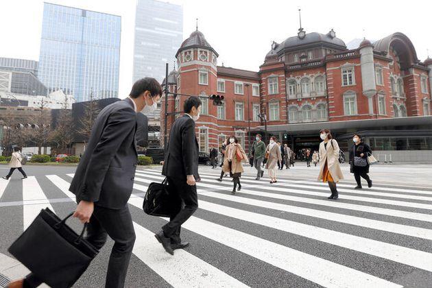 通勤客がまばらなJR東京駅前の横断歩道を渡る人たち=2020年3月27日午前8時26分、東京・丸の内、遠藤啓生撮影