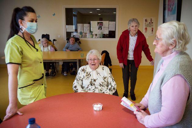 Au début de l'épidémie de coronavirus en France, une infirmière portant un masque s'occupe de patientes...