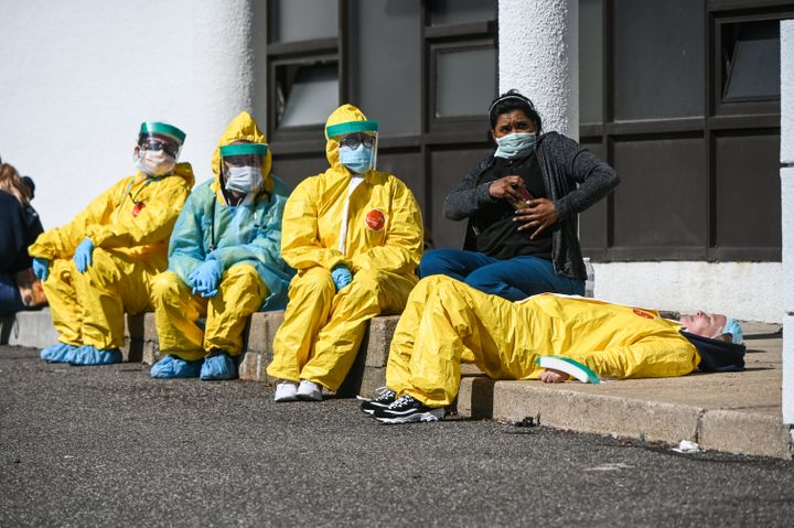 Health care professionals take a break awaiting patients as they test for COVID-19 at a testing site in Jericho, New York.