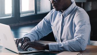 Unreconizable banner of young african american business man working, using laptop at office while sitting at table with papers and cup of coffee, typing message on computer keyboard