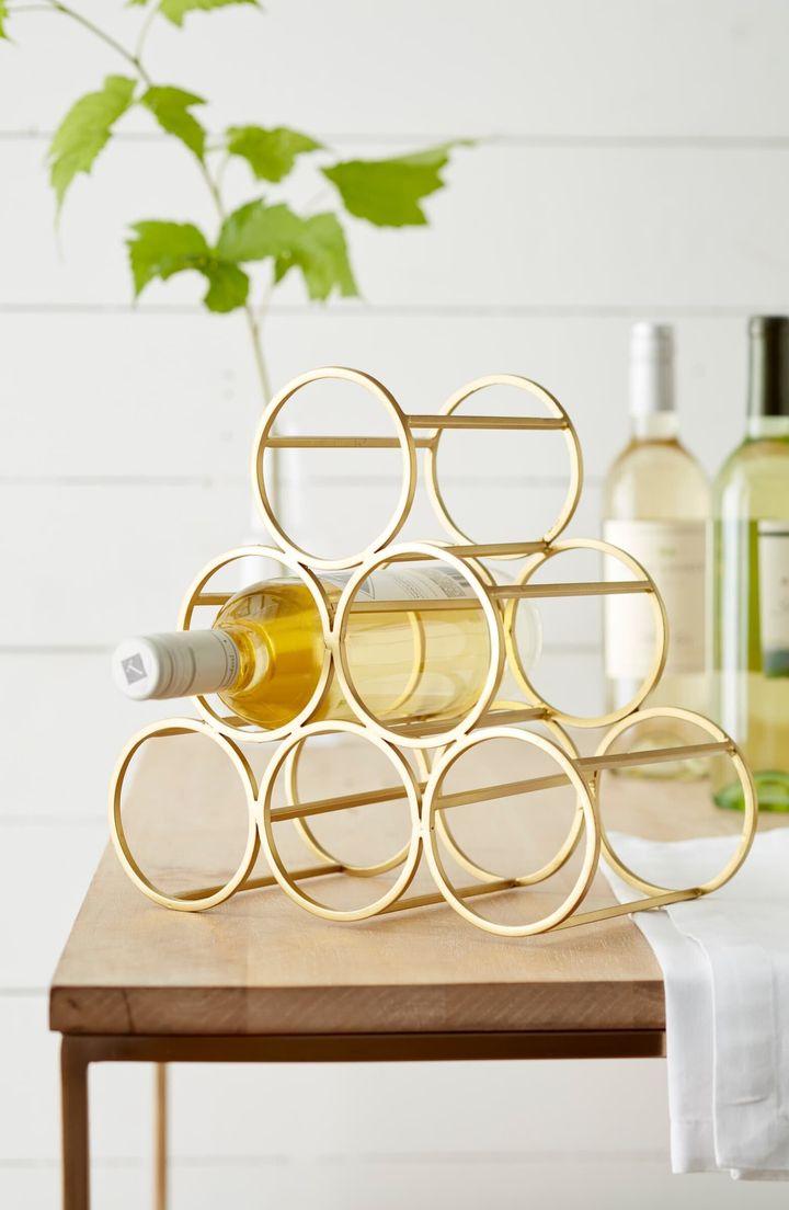 A brushed goldtone finish lends elegant shine to a graceful metal wine rack sized to hold six bottles of your favorite vintage.