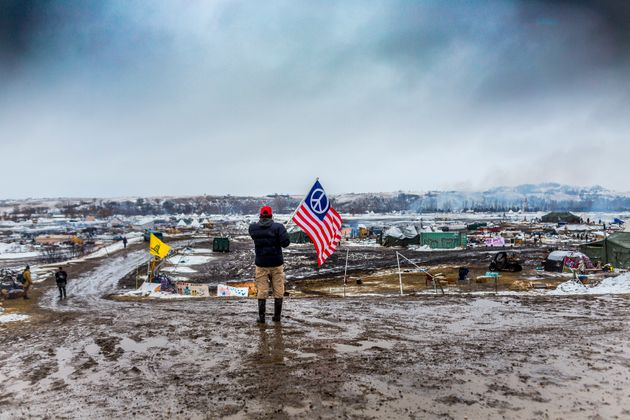 A defiant Dakota Access pipeline protester faces off against militarized police in 2017 as law enforcement...