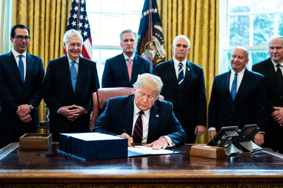 U.S. President Donald Trump signs H.R. 748, the CARES Act in the Oval Office of the White House on March...