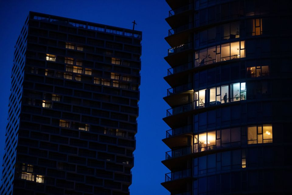 A man stands in the window of an upper floor condo as people have been urged to stay home to help prevent...