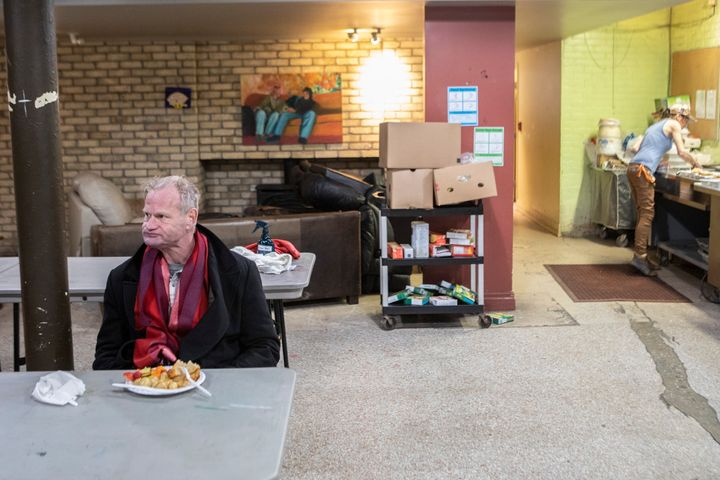 "A man sits for a meal served at The Sanctuary Drop-In Centre in Toronto on March 26, 2020. People who work with the city's homeless say more are on the streets because many drop-in and respite sites, have warned of an ""explosion"" of COVID-19 within within Toronto's homeless population."