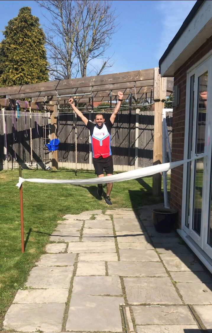 James Page crossing a toilet roll finishing line after running a marathon in his back garden in Sidcup.