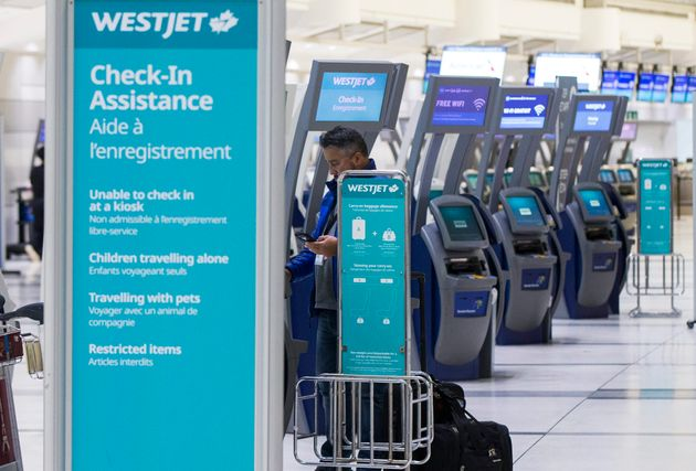 A traveller picks up boarding pass at the WestJet check-in express service area of Toronto Pearson International...