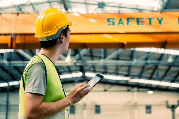 Young Asian male heavy industral worker using a digital tablet inside manufacturing and factory site...