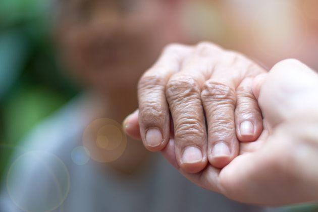 Caregiver, carer hand holding elder hand woman in hospice care. Philanthropy kindness to disabled concept.Public...