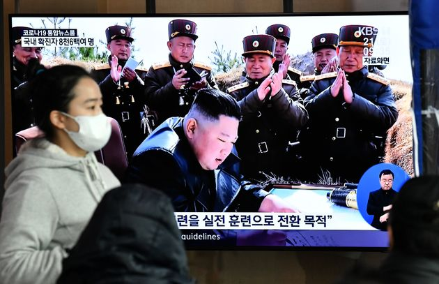 A woman wearing a face mask walks past a television news screen showing a file image of North Korean...