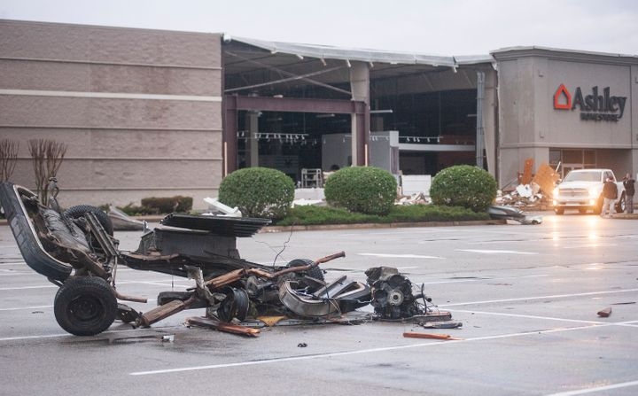 The damaged remains of a vehicle lie in a parking lot in front of a damaged Ashley Homestore after a tornado stuck Saturday,