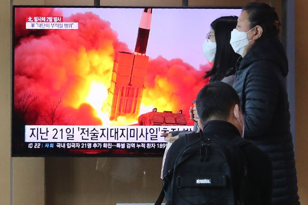 People pass by a TV screen showing a file image of North Korea's missile launch during a news program...