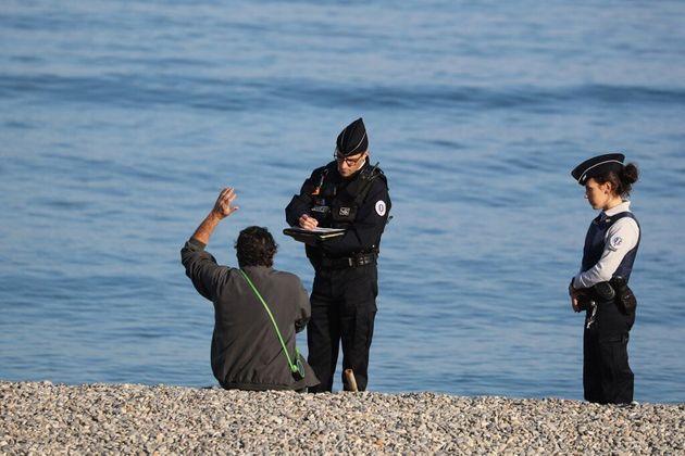 Un homme verbalisé par des policiers sur la plage de Nice, dans les Alpes-Maritimes, le 19 mars 2020...