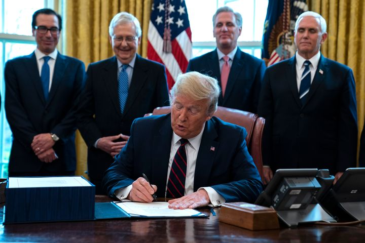 President Donald Trump signed the $2 trillion coronavirus stimulus relief package in the Oval Office at the White House on Fr