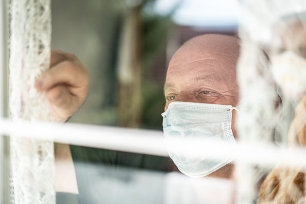 Senior man with mask looking trough