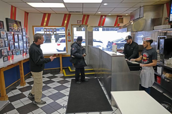 Customers, keeping their distance from one another, wait to pick up food at the famous American Coney Island diner in Detroit