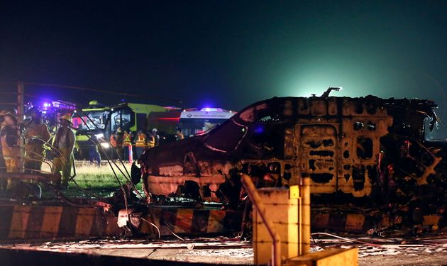 Firemen and rescuers talk beside the remains of a Lion Air, West Wind 24 aircraft after it caught fire...