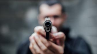 A man is pointing a gun directly at the lens.