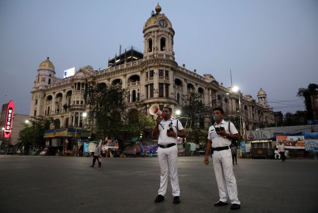 A police officer uses a megaphone advising people to vacate the roads after the lockdown by West Bengal...