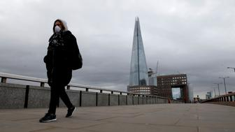 A woman wears a mask as she walks across London Bridge in London on March 30, 2020, as life in Britain continues during the nationwide lockdown to combat the novel coronavirus pandemic. - Life in locked-down Britain may not return to normal for six months or longer as it battles the coronavirus outbreak, a top health official warned on Sunday, as the death toll reached passed 1,200. (Photo by Tolga AKMEN / AFP) (Photo by TOLGA AKMEN/AFP via Getty Images)