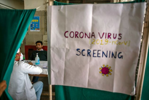 A doctor examines a patient in an area set aside for possible coronavirus cases during a free screening...