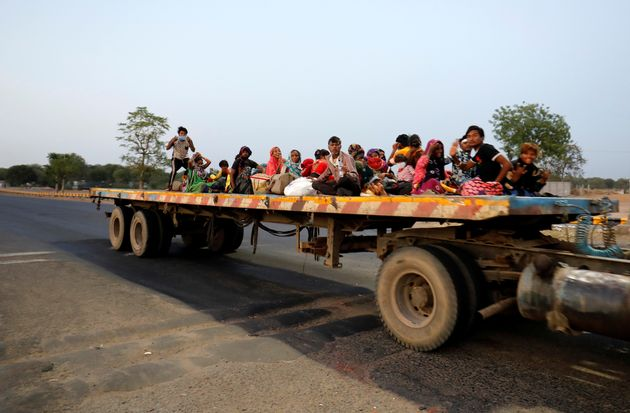 Migrant workers and their families travel in a trailer truck as they return to their villages during...