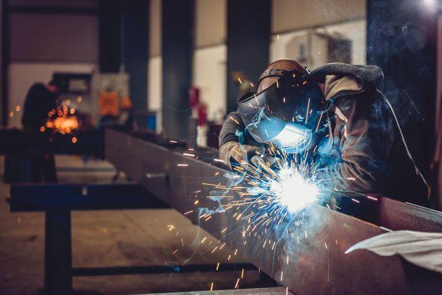 Industrial Welder With Torch and Protective Helmet in big hall welding metal