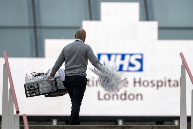 A man enters the NHS Nightingale hospital with PPE equipment at the Excel on March 30, 2020 in...