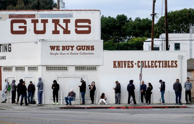 People wait in a line to enter a gun store in Culver City, Calif., Sun. March 15, 2020. Some U.S. states...