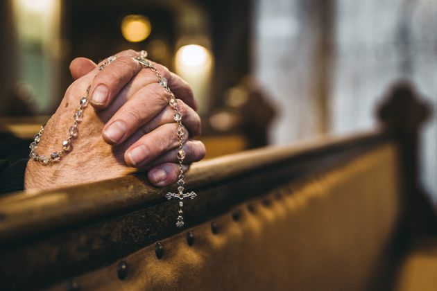 Praying senior hands with rosary in church