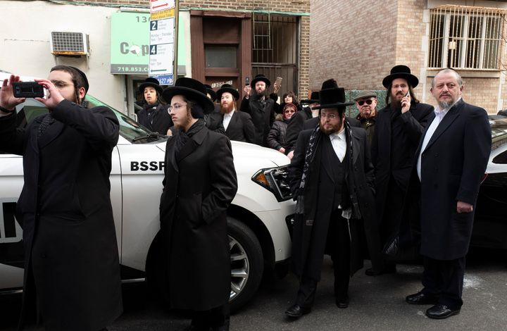 Members of the Borough Park community watch for U.S. Attorney William Barr as he leaves a meeting with Jewish leaders at the