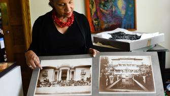 WASHINGTON, DC - JUNE 24:   A'Lelia Bundles, 64, of DC, is a descendant of Madam C. J. Walker, who was the first black woman millionaire in the United States. Bundles looks at two pictures of Walker agents during the convention in the summer of 1924. They came to mansion, Villa Lewaro, the home designed for Madam C. J. Walker in Irvington, New York in Westchester County by Vertner Tandy, the first licensed black architect in New York. She moved into the home in May 1918, a year before her death. Her daughter then lived there. Today it is a National Historic Landmark as well as a National Trust for Historic Preservation National Treasure. (Photo by Sarah L. Voisin/The Washington Post via Getty Images)