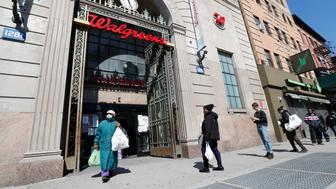 A woman leaves a Walgreens pharmacy that is enforcing social distancing rules by allowing only certain numbers of people as customers line up on the sidewalk outside the store, Thursday, March 26, 2020, in New York. Maintaining a distance of six feet from others is recommended during the current coronavirus pandemic. (AP Photo/Kathy Willens)